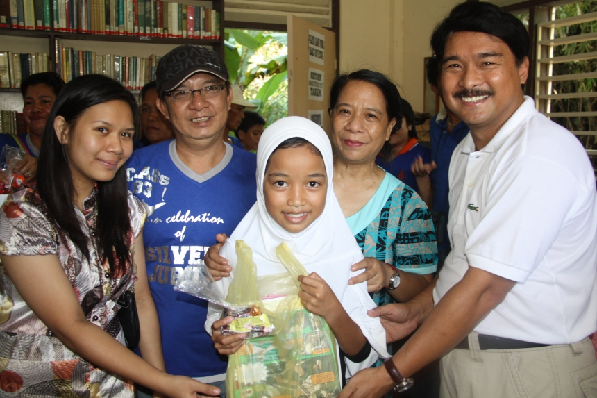 Kaisa Helping Poor Kids Amid Fresh Violence in Mindanao. Sitti B. Azib (center), an outstanding scholar of the Kristiyano-Islam Peace Library (Kris), receives school supplies during a recent gift-giving activity at the Kris Peace Library in Manicahan, Zamboanga City. Armand Nocum (right) and Flor Nocum (beside Nocum), Kris founder and donor, respectively, will open the 4th library in Tungawan, Zamboanga del Sur and distribute books and school supplies to poor children who swim to school in Layag Layag, Zamboanga City. The Kaisa Para sa Kaunlaran Inc (Kaisa), one of the country's leading Filipino-Chinese organizations, have donated school supplies to poor Christian and Muslim children in Tungawan and Layag Layag. Photo by KRIS