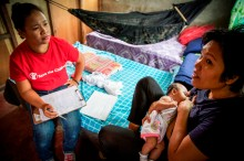 Breastfeeding Counselling in Yolanda-hit areas – A nurse from Save the Children's nutrition team visits Lolita and her two months old daugther in Palo, Leyte during a breastfeeding counselling session, a few months after Yolanda. Photo by SAVE THE CHILDREN