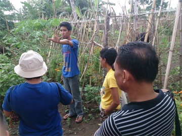 Mark of PAKISAMA tours ATM members around UNLAD's organic vegetable farm.