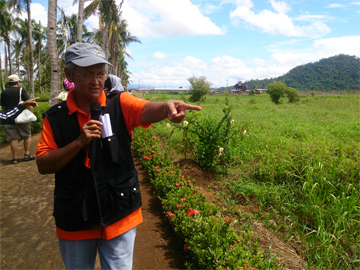 Tita Brenie shows ATM members RT Mining's operations in Maya village. One of its facilities is in the far background.
